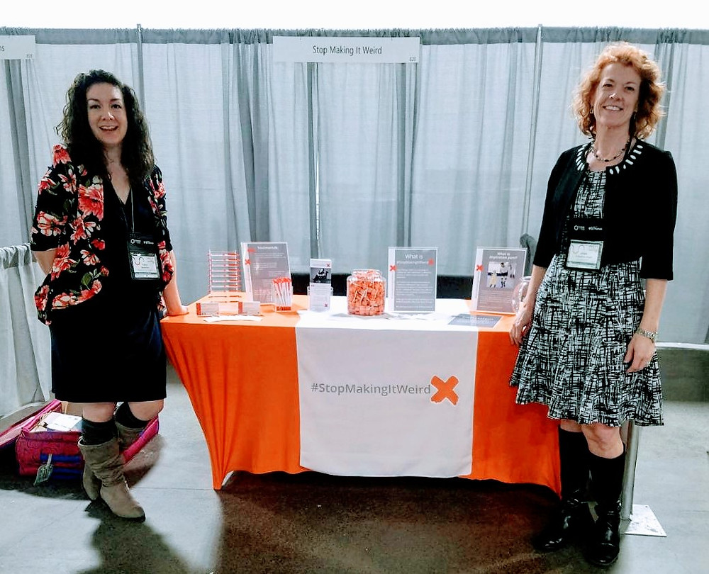 Cassy Beckman, COO and Jolene Thibedeau Boyd, CEO stand next to an orange exhibit table displaying information on Stop Making It Weird at the 2019 Forum on Workplace Inclusion in Minneapolis, MN.