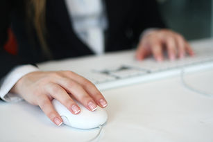 Office worker sitting in front of white desk. Right hand on white Mac Mouse, left hand on keyboard