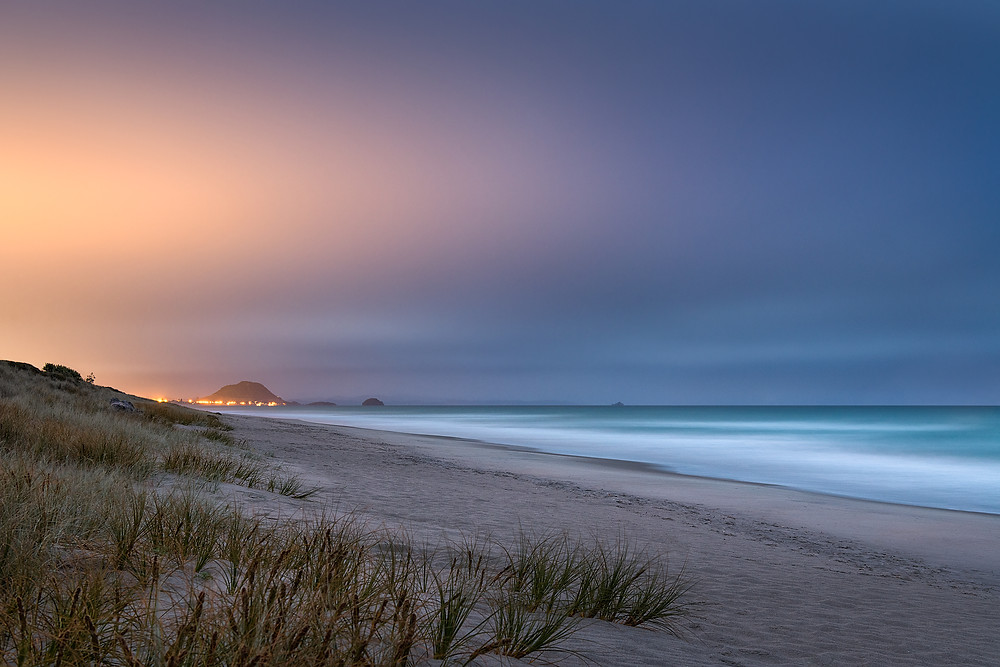 Mount Maunganui seen from Papamoa Beach with the sky lit from the night lights of the city.