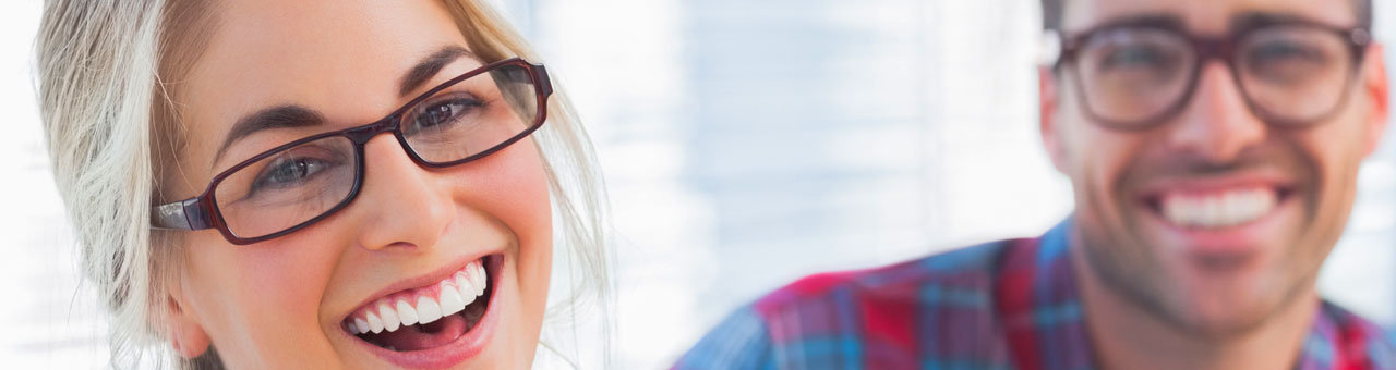 girl wearin glasses laughing, with guy in the background