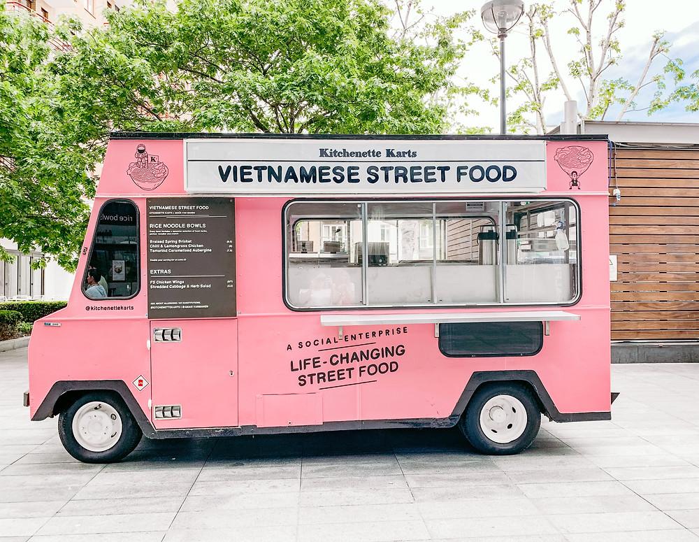 Pink Vietnamese food truck serving street food.