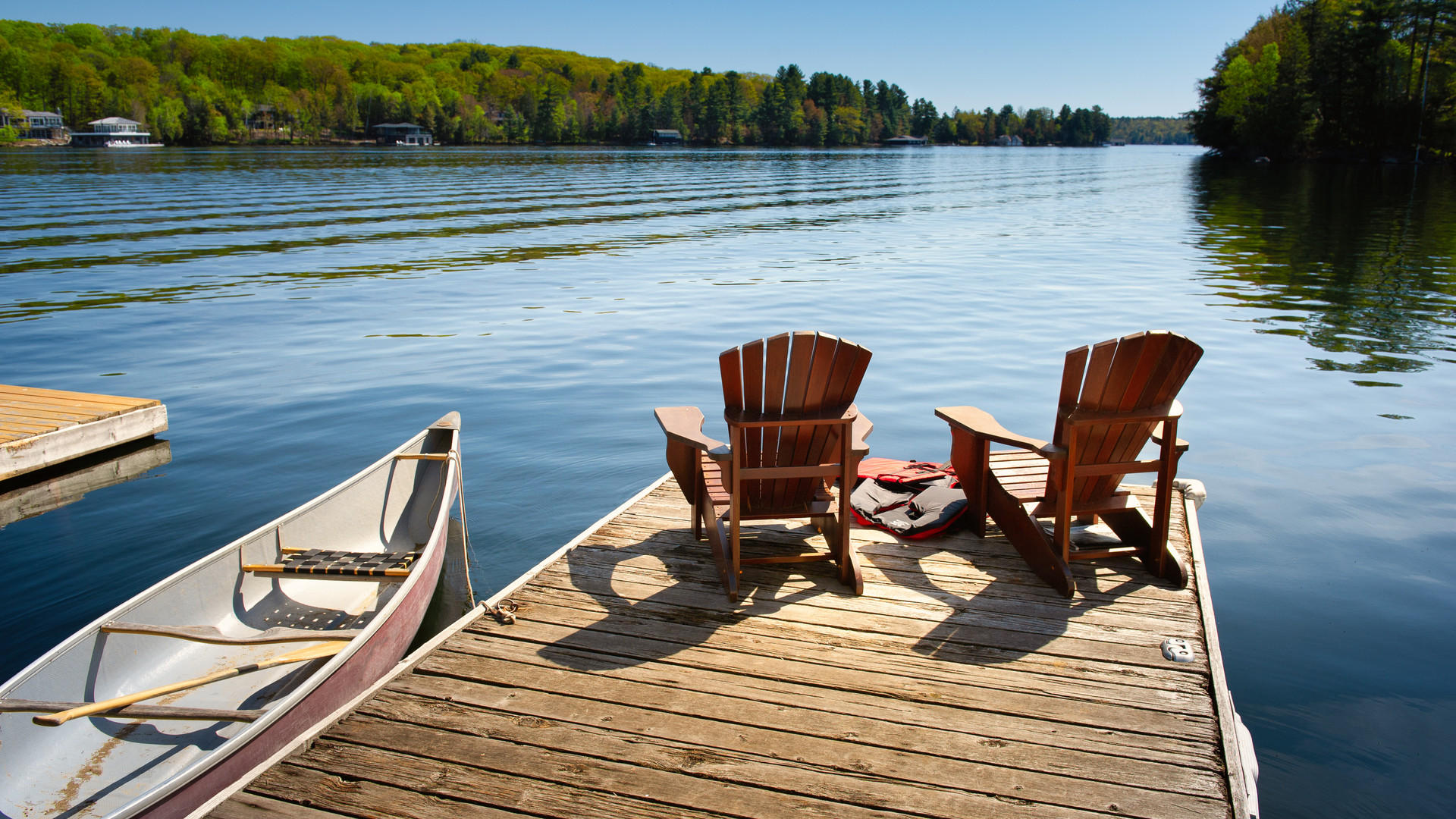 Two Adirondack chairs on a wooden dock f