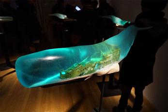 Shipwrecks And Deep Ocean Scenes Encapsulated Inside Translucent Whale Sculptures