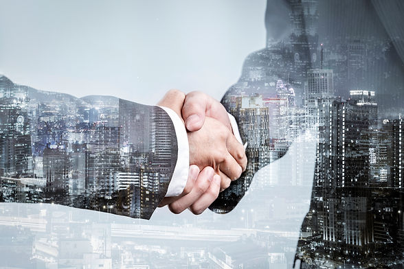 double-exposure-of-business-partnership-handshake-and-modern-city-successful-business-gree