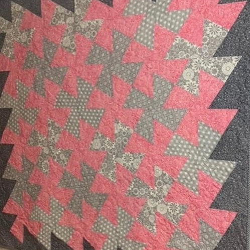 Pink and grey twister quilt