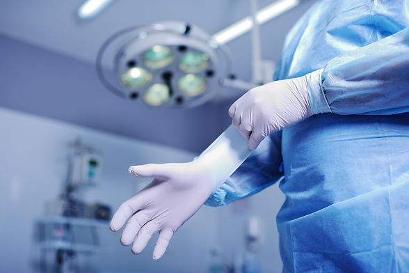 Surgeon putting on sterile rubber gloves