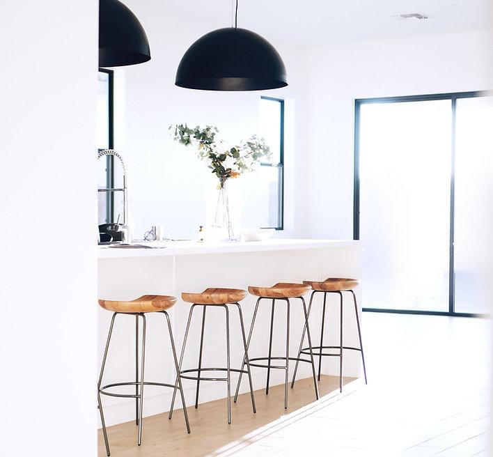 Cozinha minimalista maioritariamente branca com detalhes em verde e castanho