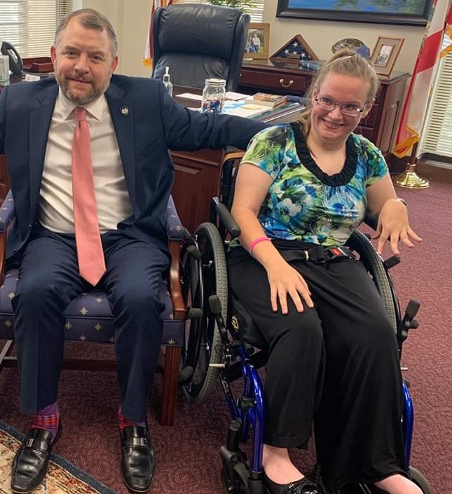 Lauren Eakin posing with Sen. Bradley. Lauren is sitting in a blue wheelchair and wearing a multicolored top and slacks, Sen. Bradley is sitting next to her, wearing a blue suit and pink tie. Both are smiling broadly.