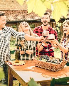 Happy friends having fun drinking wine a