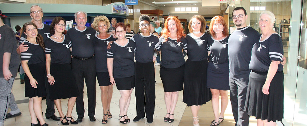 Group of smiling ballroom dancers in matching tee-shirts