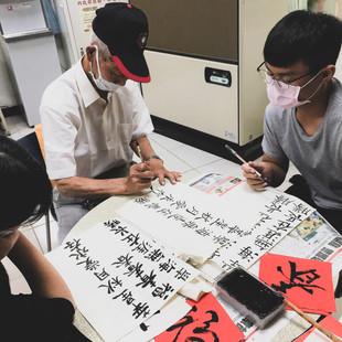 職治系學生向長勝里龔爺爺學書法.jpg
