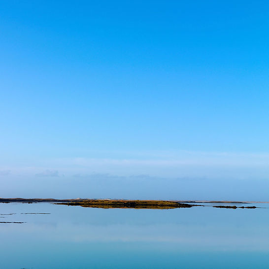The sky reflects upon the still sea waters on the western edge of the Western Isles of Scotland