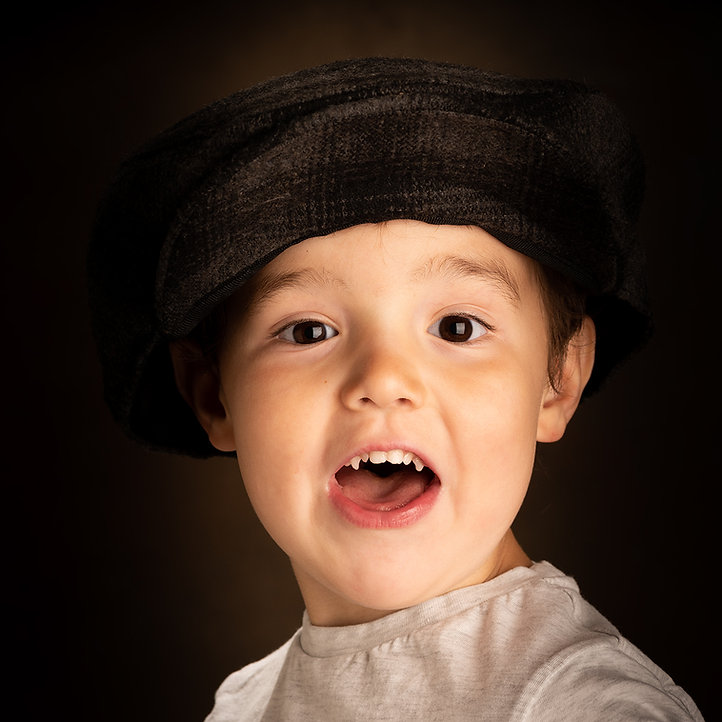 Colour studio portrait of cheeky young boy wearing a cloth cap