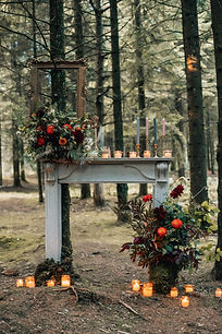woodlance ceremony space with fireplace, candles and florals