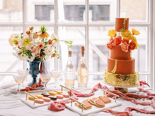 orange and gold wedding cake with sweet table