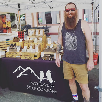 Owner Jake standing in front of his booth at a market.