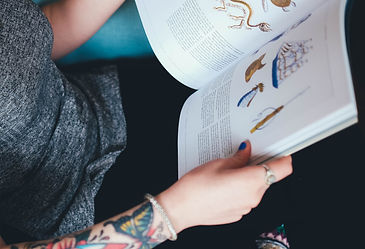 Tattooed person reading book