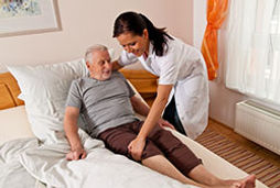 nurse assisting resident into bed