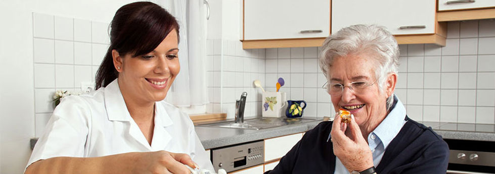 Caregiver giving breakfast to resident