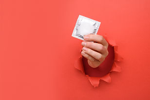 Hand give condom on torn red paper wall.