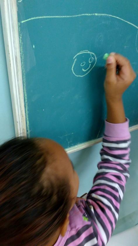 menina desenhando a lousa