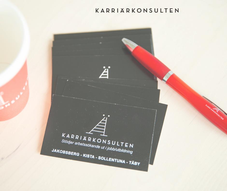Visitkort, penna och mugg med Karriärkonsultens logga på ett skrivbord.