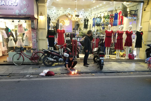 A shop worker burning offerings in the street. Vietnam is largely nonreligious, but most people practice ancestor worship.