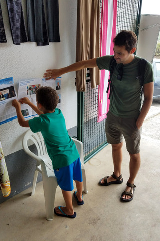 This little boy asked Brandon for help hanging a sign at the market.
