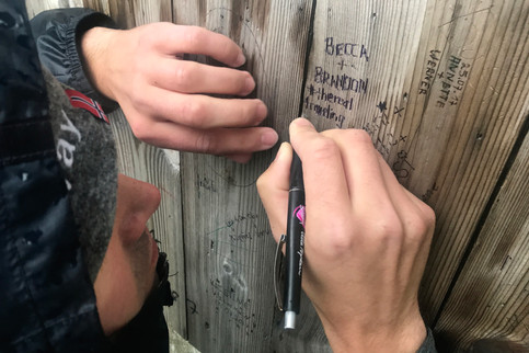 Brandon carving our names and hashtag into a shelter at the top of the mountain