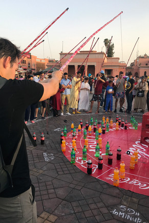 Brandon joined in this game in the square. The goal was to hook a ring over one of the soda bottles. It was super hard; no soda for us!