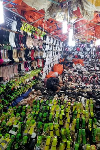 A vendor asleep in her shoe display