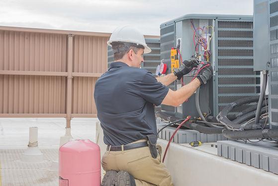 Burban Air Systems Ltd. HVAC Tech Checking Condenser