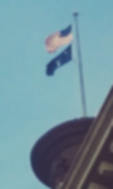 The United States and South Carolina flags on a flag pole on top of the dome of the South Carolina capitol building.