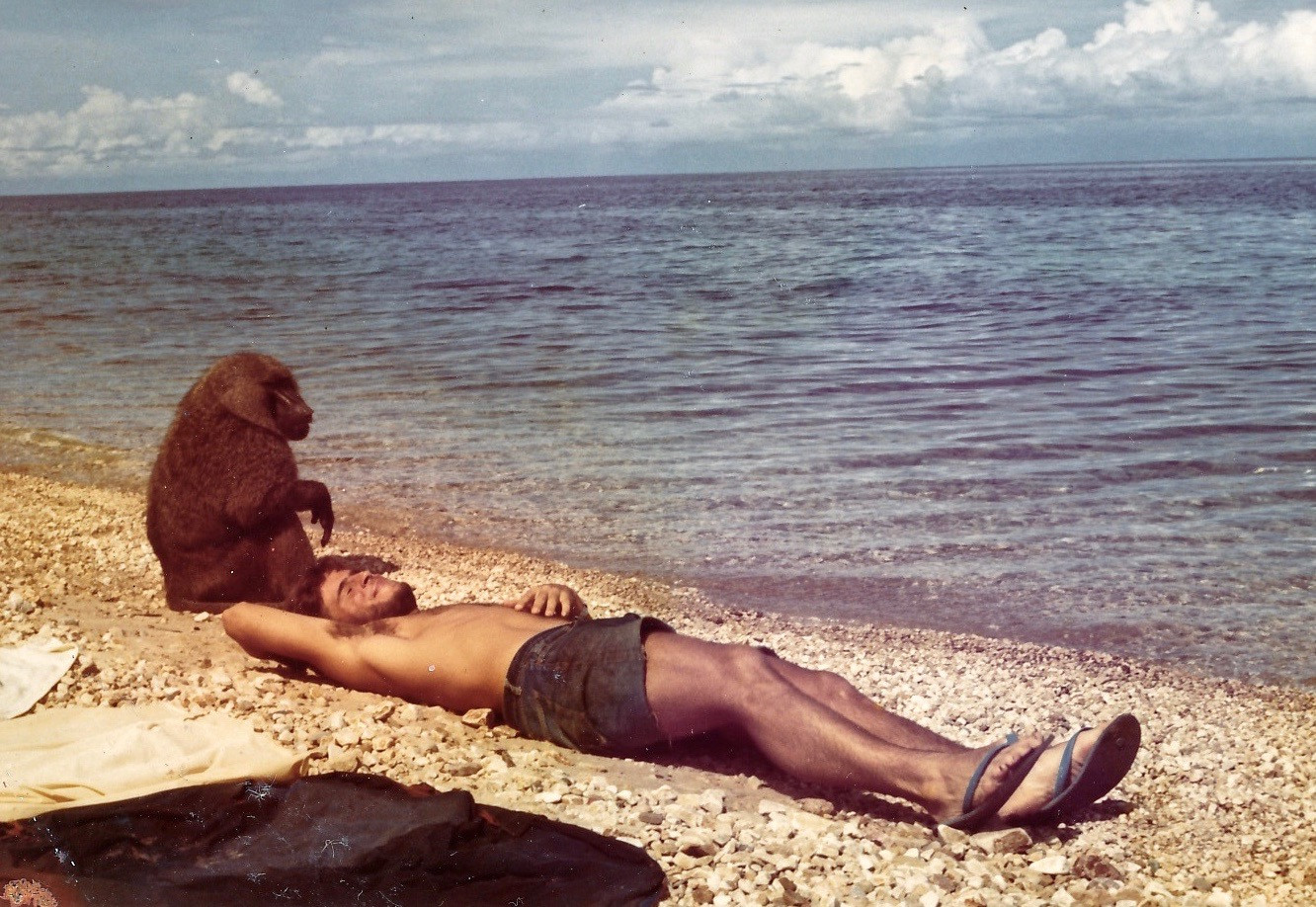 Grant Heidrich relaxing on the beach at Gombe as one of his subjects sits close by. Photo courtesy of John Crocker, 1974.