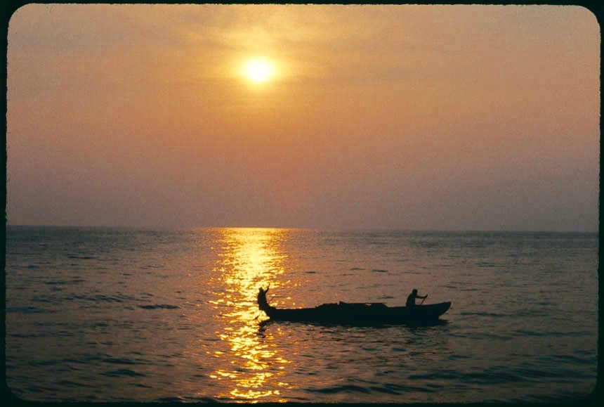 A paddler in a wooden boat at sunset brings produce back to his village from the town of Kigoma. Photo by John Crocker, 1973.
