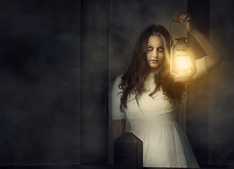 A woman eerily holds up a lantern