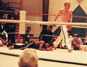 """Jerry Trimble pummelsMississippi State Golden Gloves Champion,Sam the """"Angry Man"""" Perryto the mat for the sixth time. Trainer, Asa Gordon watches on.jpg"""