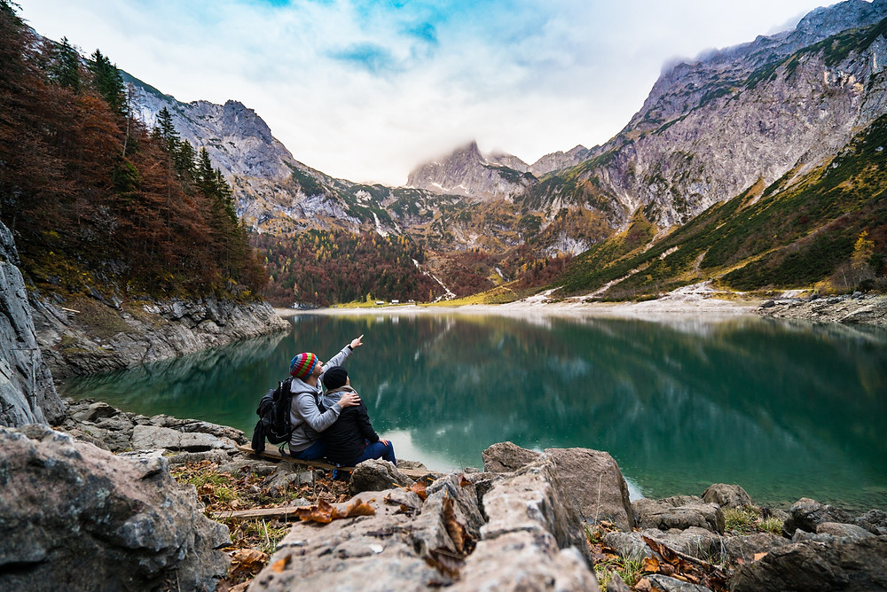 Young couple sitting by majestic turquoise lake with man pointing upwards towards surrounding mountains