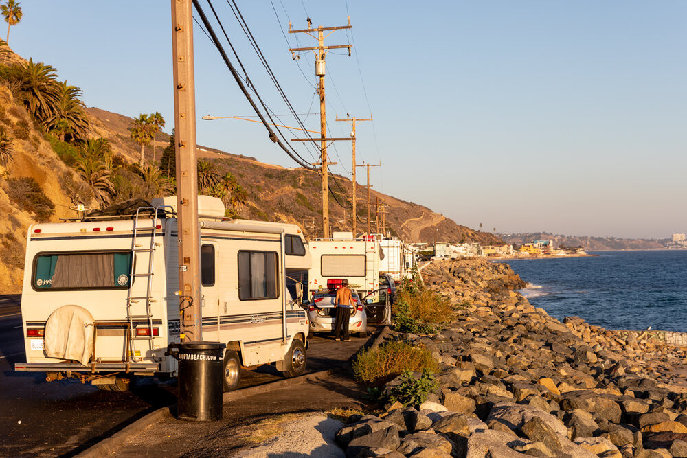 Several large Recreational Vehicles (RVs) parked in a route 1 oceanside pullout in California