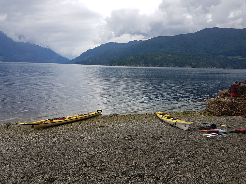 Two kayaks on rocky Olympic National Park lakeshore with paddles close by