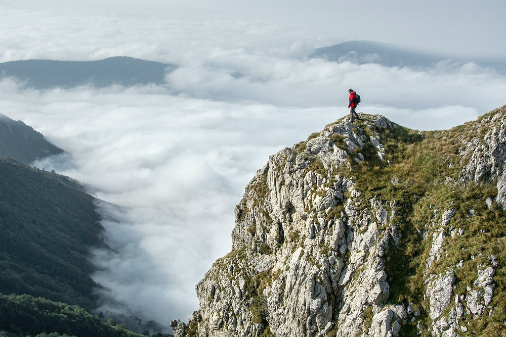 Male hiker overlooks steep drop on rocky outcropping while above layer of thick clouds below