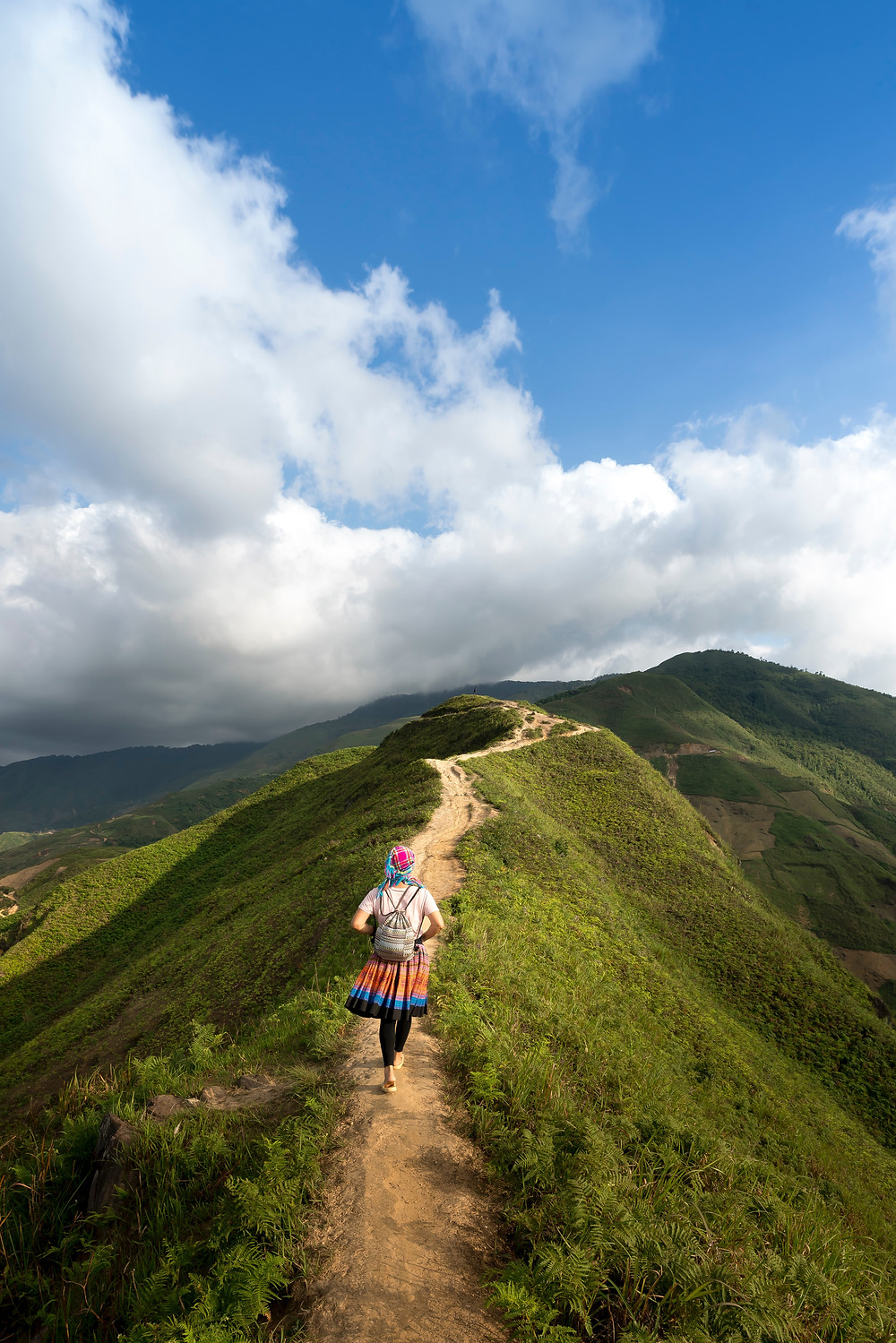Young female hiker walks along defined trail atop a green ridgeline under puffy, white, cloudy skies