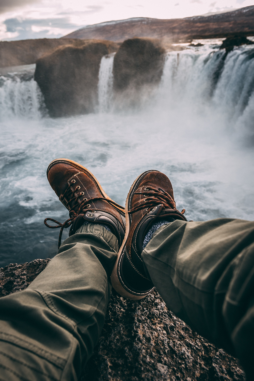 Man sits near the mist of a large, multi-stream converging waterfall wearing dressy leather shoes and dark green khaki pants