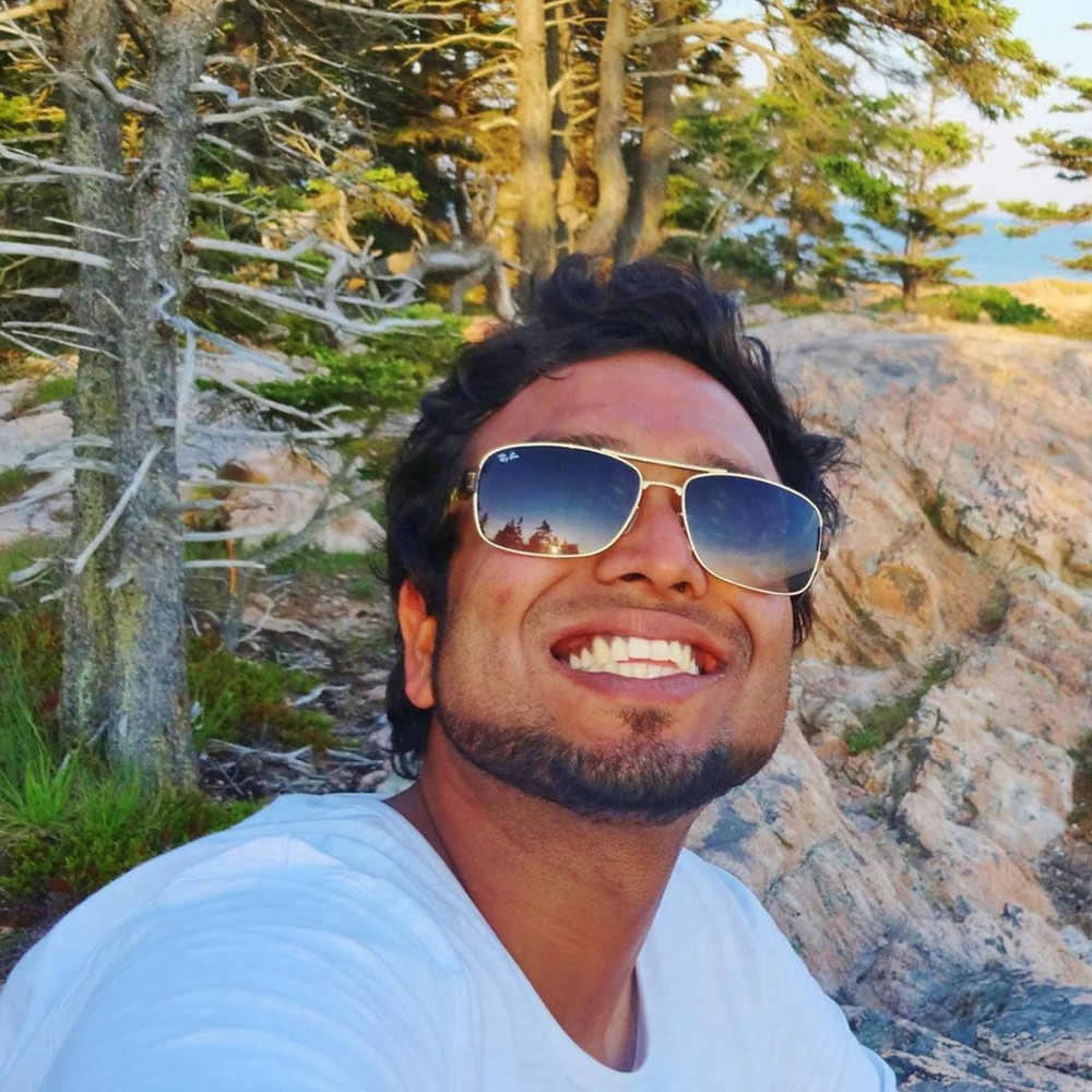Outdoor selfie image of Ankit Jain - Founder and CEO of Pathloom - in rocky outcropping under setting sun