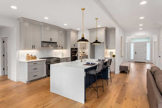 Kitchen in new luxury home with waterfall island, stainless steel appliances, pendant ligh