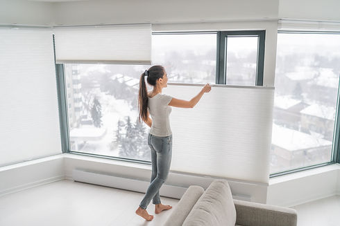 Woman opening home curtains in urban condo. Modern top down bottom up privacy cellular sha