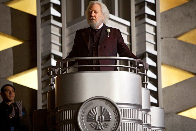 A screenshot from The Hunger Games movie. President Snow stands at a silver podium, addressing the tributes.