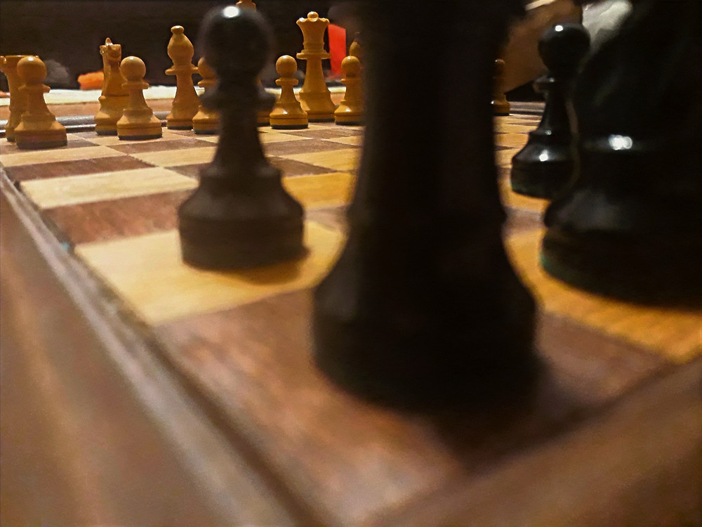 A close up image of a wooden chess set on a wooden chess board.