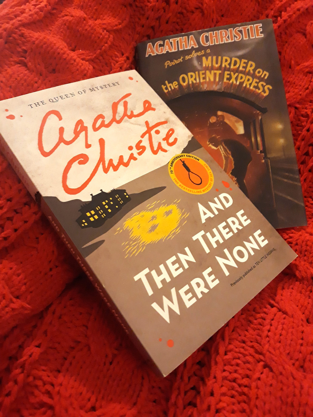 A paperback copy of And Then There Were None in front of a hardback copy of Murder on the Orient Express. They are both on a red background.