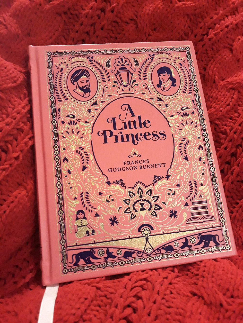 A hardcover copy of A Little Princess that is pink with black and gold foil embossing.
